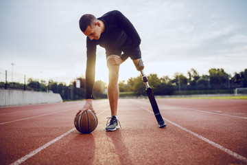Fotomurales - Full length of sporty caucasian handicapped man in sportswear and artificial leg dribble the ball while standing on racetrack.