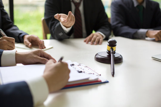 business people and lawyers discussing contract papers sitting at the table : and handshake after good cooper