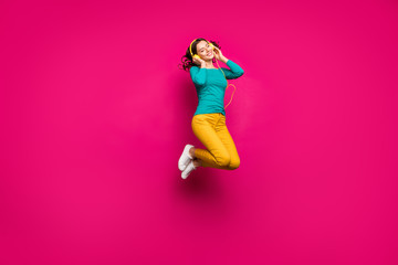 Full length body size photo of cheerful positive curly white nice cute pretty girlfriend jumping up listening to music isolated pink vibrant color background Wall mural