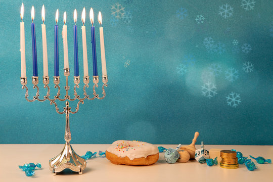 concept of of jewish religious holiday hanukkah with traditinal chandelier menorah, spinning top toys (dreidel), a doughnut and chocolate coins