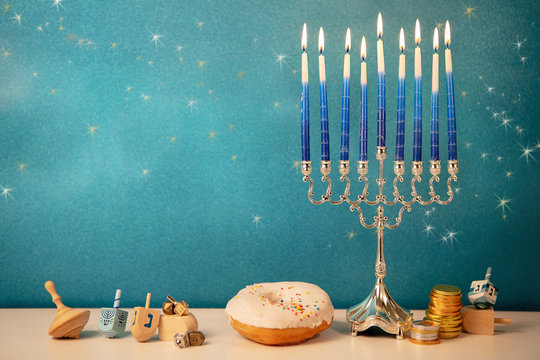 concept of of jewish religious holiday hanukkah with glittering raditional chandelier menorah, spinning top toys (dreidel), a doughnut and chocolate coins