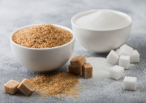 White bowl plates of natural brown and white refined sugar and cubes on light table background.