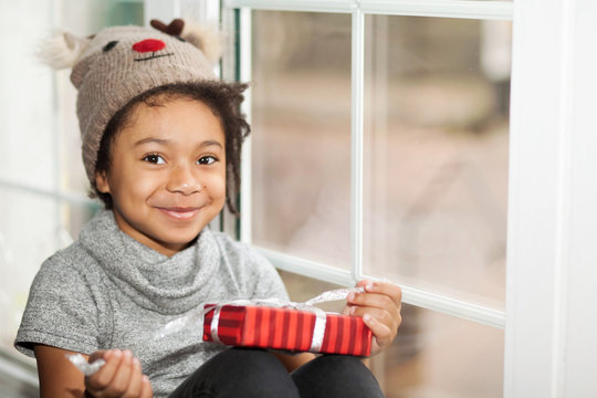 Happy adorable african american child girl opens a christmas present in a red box