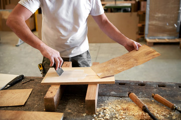 Carpenter applying glue to attach briar root panel