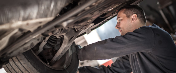 Auto master mechanic checks condition of the brakes and wheels Fototapete