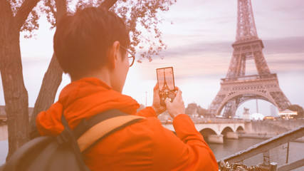 Travel tourist  which  he's a take a picture by smartphone at Eiffel tower, Paris. France