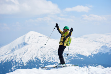 Sportsman skier in helmet and goggles with backpack standing on skis holding ski poles in raised arms, in deep white snow on copy space background of bright blue sky and beautiful mountain view.