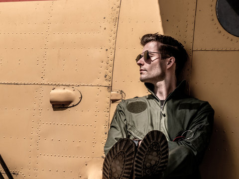 A handsome young pilot sitting on the wing of a plane