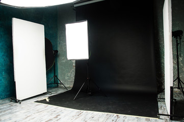 The interior of the photo studio. Preparing to work with photographic equipment. Black cyclorama, exposure to light on the octobox, softbox. Studio flags.