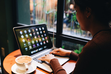 A young girl working with a cup of cappuccino coffee with laptop white screen on table. Royalty high quality free stock photo image of woman typing, working on laptop with a coffee cup in coffee shop