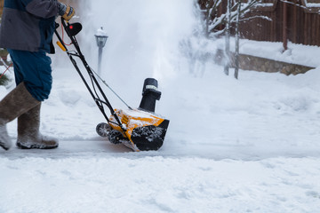 Man clears snow with a snow blower after a snowfall in house yard.. Snowblower in working.Snowy winter yard.