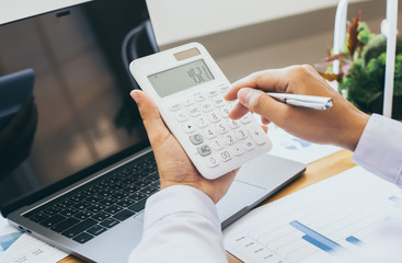 Calculate the calculator, Male employees work in private rooms Calculating company revenue figures with calculator, Financial accounting concepts