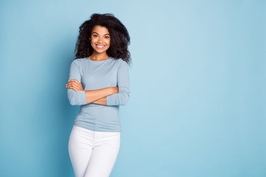 Photo of trendy cheerful cute nice pretty toothy beaming girl with hands folded in white pants near empty space isolated pastel color blue background