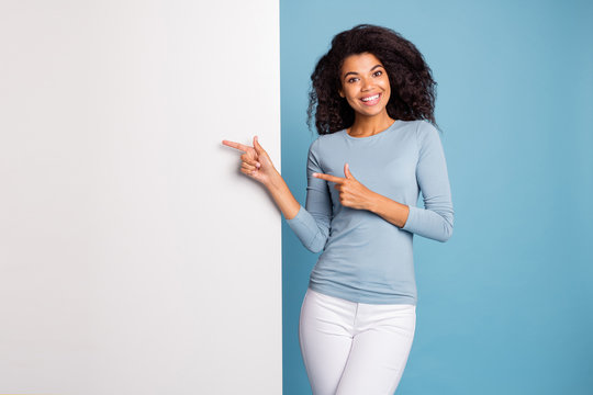 Photo of brunette haired cheerful positive cute nice curly wavy girl pointing at empty white banner space in pants trousers blue sweater smiling toothily isolated pastel color background