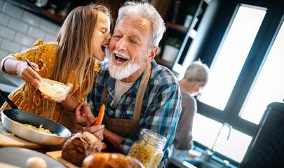 Grandfather and his grandchildren spendig happy fun time in kitchen