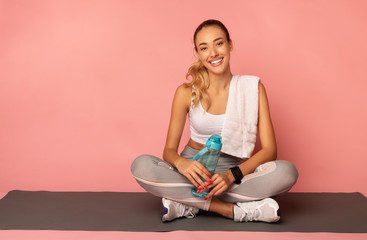 Positive Girl Sitting On Fitness Mat Resting Over Pink Background