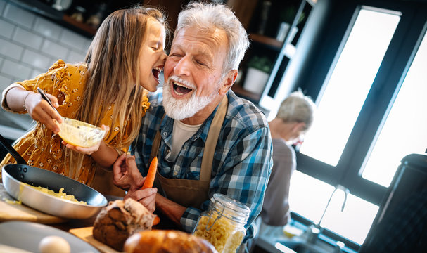Grandfather and his grandchildren spendig happy fun time in kitchen