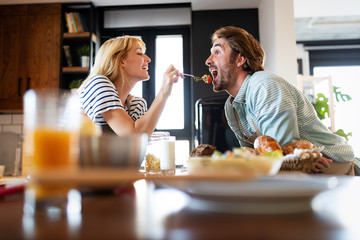 Young couple in love enjoying food together in kitchen