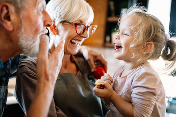 Happy grandparents playing with their little cute granddaughter Wall mural