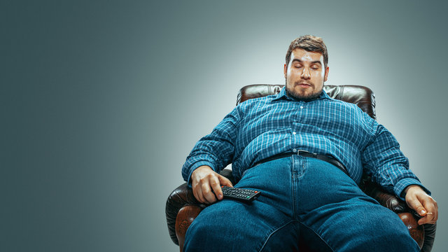 Portrait of fat caucasian man wearing jeanse and whirt sitting in a brown armchair isolated on gradient grey background. Emotional watching TV and changing channels, laughting. Overweight, carefree.