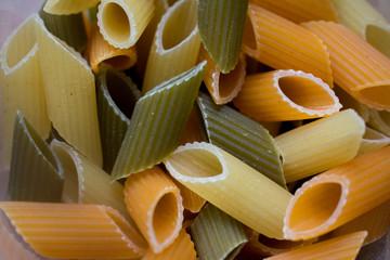 Fondo de alimentos: Macarrones de pasta de trigo duro de tres colores sin cocer, con espinacas y tomate.