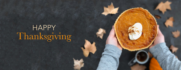 Serving a pumpkin pie on blurred background. Happy Thanksgiving text