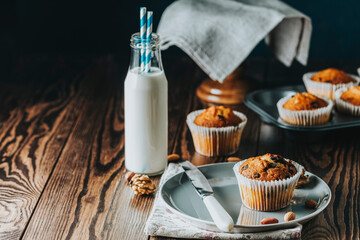 Vanilla caramel muffins in paper cups and bottles of milk on dark wooden background.