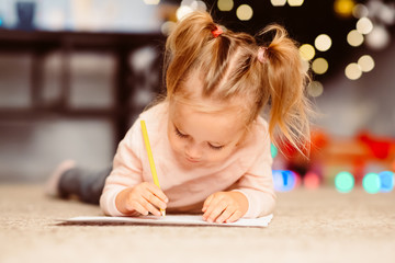 Little girl drawing letter to Santa Claus