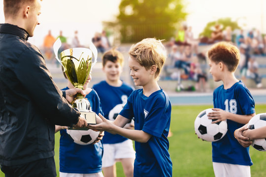 Happy Smiling Young Boys Celebrating Sports Soccer Football Championship. Team Winning Football Tournament for Youth. Sport Background. Young Soccer Player Holding Trophy. Junior Coach Hand Golden Cup