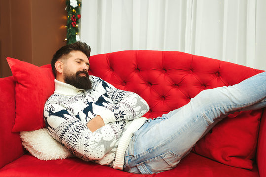 Handsome man tired while preparation christmas gifts. Christmas holidays. Young father sleeping at modern sofa in living room after xmas celebration