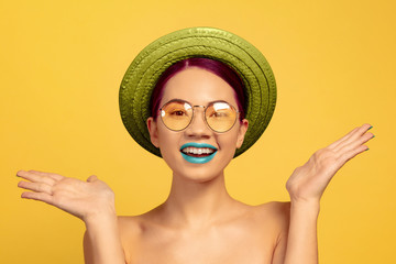 Portrait of beautiful woman with bright make-up, hat and sunglasses on yellow studio background. Stylish and fashionable make and hairstyle. Colors of summer. Beauty, fashion and ad concept. Surprised Wall mural