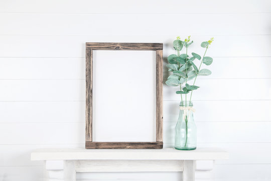 Mockup of a rough wooden frame on a white wall background in the interior