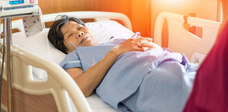 Elderly patient female lay down on hospital bed in inpatient ward with cousin visit. Geriatric doctor or geriatrician with insurance concept.