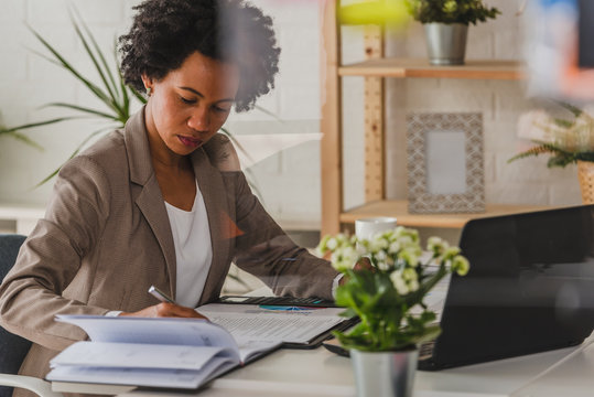 Serious african-american business woman working on laptop at office