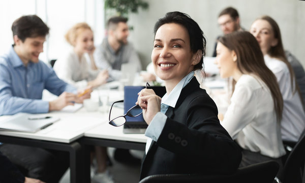 Female top manager smiling to camera at meeting