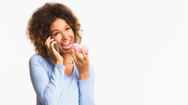 Pregnant woman eating donut and talking on phone