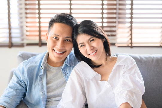 Asian couple in love smiling relaxing on sofa at home