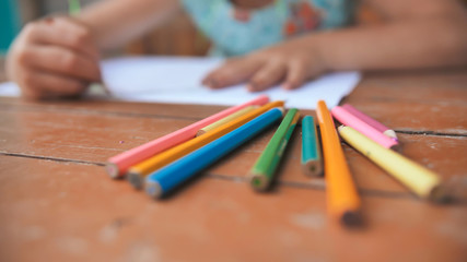 Little six-year-old girl draws with colored pencils. Close-up view of pencils.