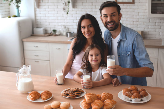 cute girl, mother and father holding cookies with milk glasses and looking at the camera and in the kitchen at home