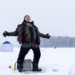 Foto auf AluDibond Wintersport Happy shouting adult fisherman after successful winter fishing a