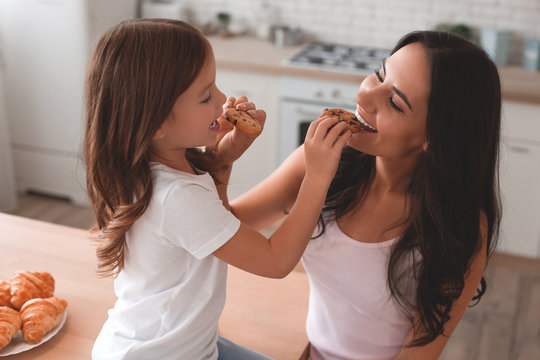 portrait of mother and daughter feeding each other with biscuits on the kitchen