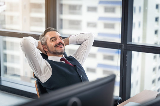 happy young businessman work in modern office relaxing in chair, lifestyle after work at office sitting hands behind head for happy businessmen people
