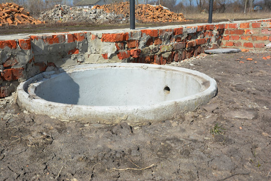 Installing concrete septic tank. Sewer tank hole installation outdoors