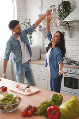 husband and wife dancing on the kitchen while preparing dinner