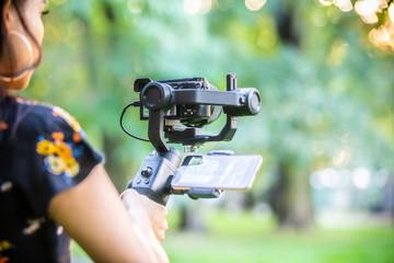 A girl operating camera mounted on a gimbal.