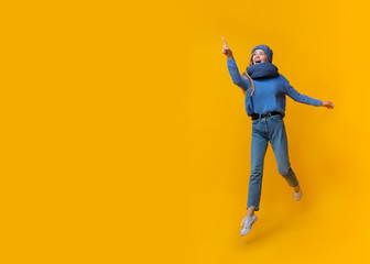 Emotional winter girl pointing at copy space over yellow background