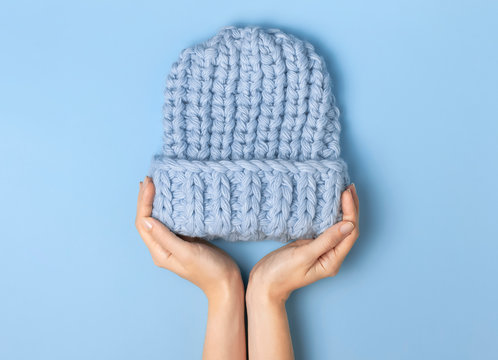 Flat lay fashionable blue knitted winter hat in female hands on blue background top view. Stylish woolen hat, concept of winter accessories for the cold. Advertising, shopping, winter sale