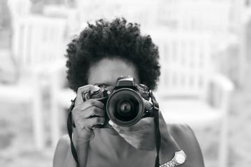 Chica con pelo afro tomando una fotos con cámara reflex