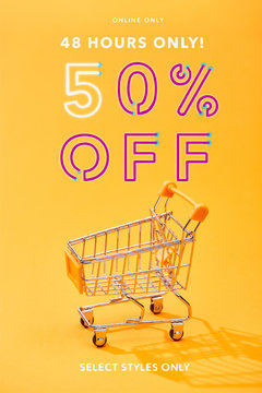 empty small shopping cart on bright orange background with 48 hours only 50 percent off illustration