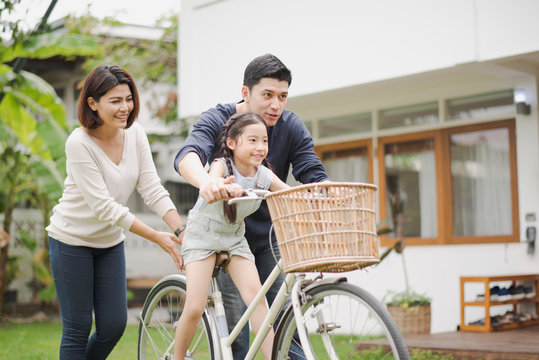 Young Asian family love, father and mother teach and training daughter to ride a bike on grass field at outdoor of home. girl train to ride a bike by her parent which smiling and felling happy